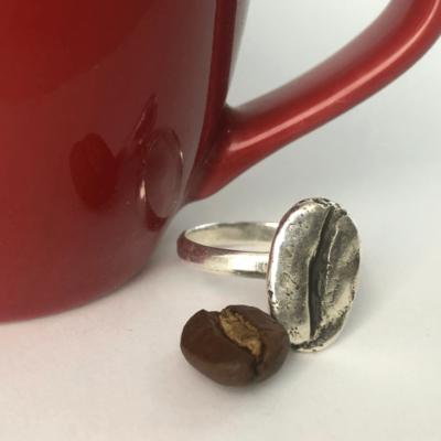 anillo de grano grande de cafe marago hecho en plata sobre una taza roja de espresso